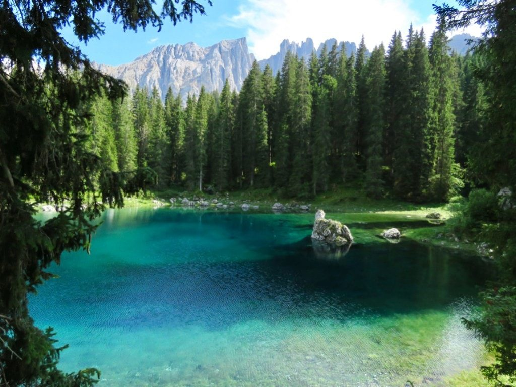Dolomites Italy hiking - Lake Carezza in the summer sun with Latemar Mountain in the background